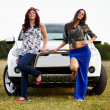 Beautiful ladies sitting on a car — Foto de Stock
