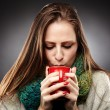 Woman with flu wrapped up in a scarf and drinking hot tea — Stock Photo