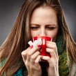 Woman feeling sick with a cold, wrapped up in a woolly scarf and — Stock Photo