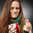 Womwrapped up in scarf and holding cup of hot teexpress — Stock Photo #38719735