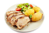 Baked tenderloin garnished with potatoes, lettuce and tomatoes o — Stock Photo