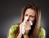 Caucasian female with flu blowing her nose — Stock Photo