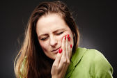 Young woman having a severe tooth ache with hand on cheek — Stock Photo