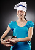 Cheerful woman chef wearing hat and holding a po — Stock Photo