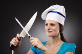 Woman chef sharpening the knife — Stock Photo