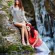 Two beautiful young women leaning on rocks beside a river — Stock Photo