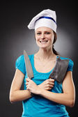 Woman chef holding a knife and a chopper — Stock Photo