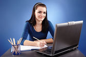 Young woman working with laptop on blue background — Stockfoto