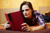 Young lady reading a book on the bed — Stock Photo