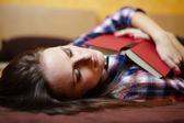 Young lady sleeping with a book on the bed — Stock Photo