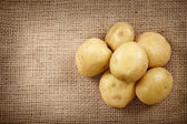 Potatoes on a rustic canvas — Stock Photo