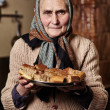 Old woman with homemade cookies — Stock Photo