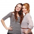 Happy girlfriends standing embraced and smiling — Stock Photo