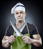Menacing man cook holding two sharp knives — Stock Photo
