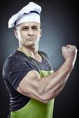 Muscular man cook displaying his biceps — Stock Photo