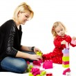 Mother and son playing with colorful cubes sitting on the floor — Stock Photo #42177327