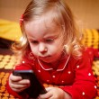 Stock Photo: Girl toddler laying in bed and holding a smartphone
