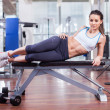 Athletic woman resting on a bench at the gym — Stock Photo