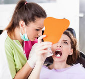Patient looking in the mirror at her teeth — Stock Photo