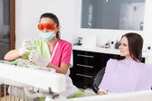 Woman dentist and patient in a dental clinic — Stockfoto