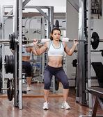 Спортивная(ый) женщина, делая приседания в тренажерном зале — Стоковое фото