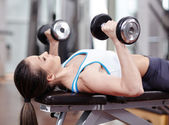 Woman working triceps and chest with dumbbells — Stock Photo