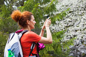 Woman hiker taking photos with cellphone — Стоковое фото