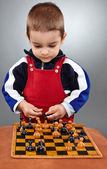 Kid learning to play chess — Stock Photo