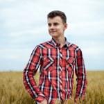 Teenage boy in a wheat field — Stock Photo #48409377
