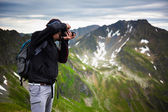 Hiker taking photos of landscape — Stock Photo