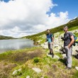 Hikers nearby a lake in the mountains — Stock Photo #49811895