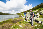 Hikers nearby a lake in the mountains — Stock Photo