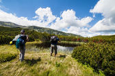 Hikers nearby a lake in the mountains — Stok fotoğraf