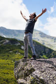 Happy young man in the mountains — Stock Photo
