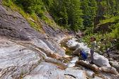 Tourist taking photos of a waterfall — Stock Photo