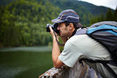Tourist taking photos of a lake — Stock Photo