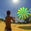 Stock Photo: Man prepares a parachute for tourists on the beach