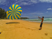 Man prepares a parachute for tourists on the beach — Stock Photo