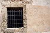 Old window with metallic grids on a clear stones wall — Stock Photo