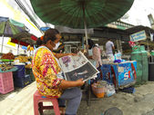 Man reading newspaper at the market — Stock fotografie