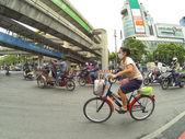 Woman on bike rides among scooters — Zdjęcie stockowe