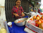 Woman squeezes pomegranate juice in the  market — Stockfoto
