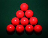 A set of red snooker balls in a triangle on green pool table — Stock Photo