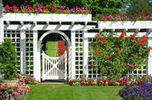 White garden gate with flowers — Stock Photo