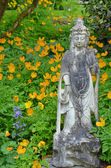 Asian statue in flower garden — Stock Photo