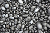 Black lava pebbles on beach — Stock Photo