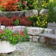 Stone wall, bench and plants on colorful landscaped garden. — Stockfoto
