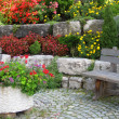 Stone wall, bench and plants on colorful landscaped garden. — Foto de Stock