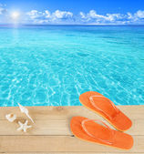 Sandals by a tropical pool — Stock Photo