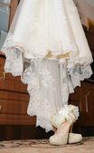 Sapatos com liga e vestido de noiva — Fotografia Stock